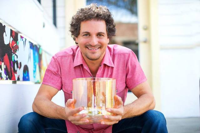David Kennet holding a crystal singing bowl that he uses in his soul sounding sessions.